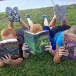 3 children lying in grass, reading