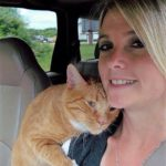 Woman in car with orange cat