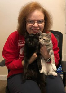 woman in red sweater holding 2 cats
