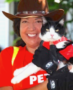 woman in cowboy hat holding black cat