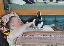 cat lying on computer; man trying to type