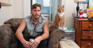 cat sitting next to man