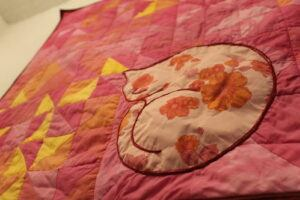 flowered cat on pink quilt